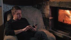 Retrato del hombre joven con la tableta cerca de la chimenea almacen de video