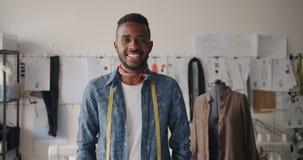 Retrato del hombre joven creativo de African American del sastre que sonríe en estudio metrajes