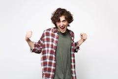 Retrato del hombre joven de griterío extático en puños de apretón de la ropa casual como el ganador aislado en la pared blanca fotografía de archivo libre de regalías