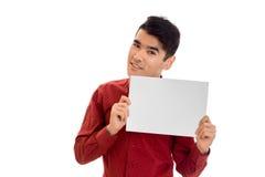 Retrato del hombre joven de moda en camiseta roja con el cartel vacío en sus manos aisladas en el fondo blanco Fotos de archivo libres de regalías