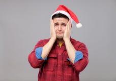 Retrato del hombre joven del trastorno en el sombrero rojo de Papá Noel Fotografía de archivo
