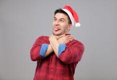 Retrato del hombre joven del trastorno en el sombrero rojo de Papá Noel Imagenes de archivo