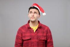 Retrato del hombre joven del trastorno en el sombrero rojo de Papá Noel Fotos de archivo