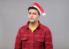 Retrato del hombre joven del trastorno en el sombrero rojo de Papá Noel Fotos de archivo libres de regalías