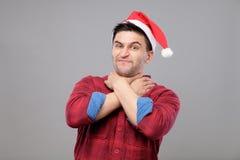 Retrato del hombre joven del trastorno en el sombrero rojo de Papá Noel Foto de archivo libre de regalías