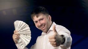 Retrato del hombre joven emocionado que agita mucho dinero y que muestra sus emociones a la cámara almacen de metraje de vídeo