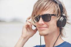 Retrato del hombre joven en auriculares y gafas de sol en la playa Fotografía de archivo