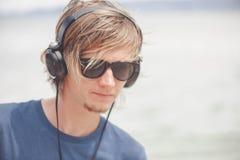 Retrato del hombre joven en auriculares y gafas de sol en la playa Imagen de archivo