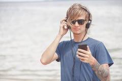 Retrato del hombre joven en auriculares y gafas de sol en la playa Imagen de archivo libre de regalías