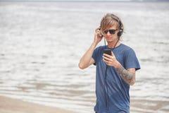 Retrato del hombre joven en auriculares y gafas de sol en la playa Fotografía de archivo libre de regalías