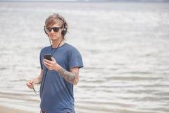 Retrato del hombre joven en auriculares y gafas de sol en la playa Imágenes de archivo libres de regalías