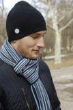 Retrato del hombre joven en casquillo y bufanda negros Fotos de archivo libres de regalías