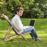 Retrato del hombre joven en el perfil que se sienta con el ordenador portátil Fotos de archivo libres de regalías