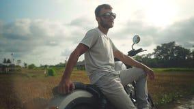 Retrato del hombre joven en los vidrios que se sientan en la motocicleta almacen de metraje de vídeo