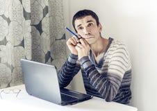 Retrato del hombre joven en ropa de sport en el funcionamiento del trabajo en el ordenador port?til que mira con la cara pensativ imagen de archivo libre de regalías