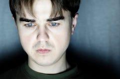 Retrato del hombre joven en sitio oscuro en el fondo oscuro, hombre joven que trabaja en el ordenador, codificación seria del pro Fotos de archivo