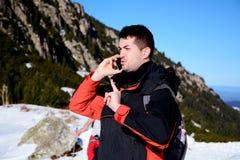 Retrato del hombre joven enojado que habla en el teléfono en la montaña del invierno Foto de archivo