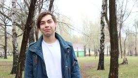 Retrato del hombre joven feliz caucásico hermoso que sonríe en cámara en el parque almacen de video