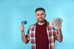 Retrato del hombre joven feliz con la tarjeta del dinero y de crédito en fondo imágenes de archivo libres de regalías