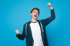 Retrato del hombre joven feliz extático en los puños de apretón de la ropa casual como ganador, decir aislados sí en azul fotos de archivo