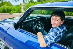 Retrato del hombre joven feliz que conduce el coche azul Fotografía de archivo libre de regalías