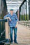 Retrato del hombre joven feliz que se coloca en el puente Fotografía de archivo