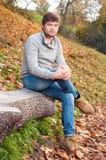 Retrato del hombre joven feliz que se sienta en parque del otoño Fotografía de archivo libre de regalías