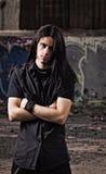 Retrato del hombre joven hermoso con el pelo largo entre ruinas industriales Imagenes de archivo