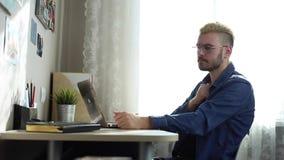 Retrato del hombre joven hermoso en vidrios con el pulgar amarillo de las demostraciones del pelo en la cámara Freelancer casero  almacen de video