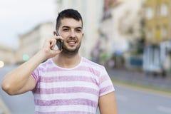 Retrato del hombre joven hermoso que habla en el teléfono al aire libre Foto de archivo libre de regalías