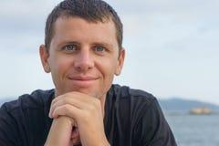 Retrato del hombre joven hermoso que se opone a una playa Fotografía de archivo