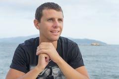 Retrato del hombre joven hermoso que se opone a una playa Imagen de archivo