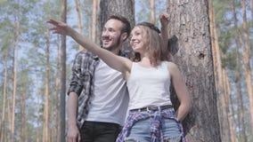 Retrato del hombre joven hermoso y de la mujer bonita que miran lejos permanentes en el concepto del bosque del pino de acampar O almacen de video