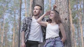 Retrato del hombre joven hermoso y de la mujer bonita que miran lejos permanentes en el concepto del bosque del pino de acampar O almacen de metraje de vídeo