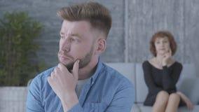 Retrato del hombre joven infeliz triste que mira lejos en el primero plano La figura borrosa de la señora madura que se sienta en almacen de metraje de vídeo