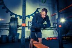 Retrato del hombre joven muscular del ajuste estupendo que se resuelve en gimnasio con el barbell Imágenes de archivo libres de regalías