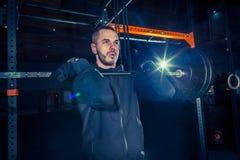 Retrato del hombre joven muscular del ajuste estupendo que se resuelve en gimnasio con el barbell Fotografía de archivo