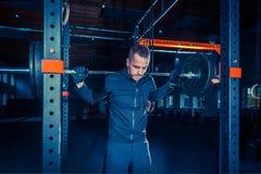 Retrato del hombre joven muscular del ajuste estupendo que se resuelve en gimnasio con el barbell Foto de archivo libre de regalías