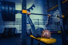 Retrato del hombre joven muscular del ajuste estupendo que se resuelve en gimnasio con el barbell Imagenes de archivo