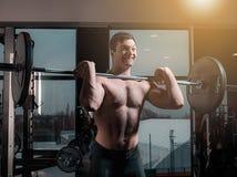 Retrato del hombre joven muscular del ajuste estupendo que se resuelve en gimnasio con el barbell Fotografía de archivo libre de regalías