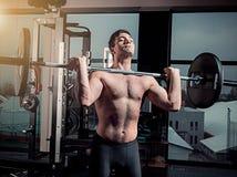 Retrato del hombre joven muscular del ajuste estupendo que se resuelve en gimnasio con el barbell Fotos de archivo