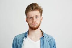 Retrato del hombre joven nervioso con la barba que mira la cámara que aumenta para arriba la frente sobre el fondo blanco Fotos de archivo libres de regalías