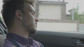 Retrato del hombre joven pensativo que se sienta en el asiento trasero del montar a caballo del coche del uber en el día lluvioso almacen de metraje de vídeo