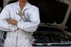 Retrato del hombre joven profesional del mecánico en llave que se sostiene uniforme contra el coche en capilla abierta en el gara foto de archivo libre de regalías
