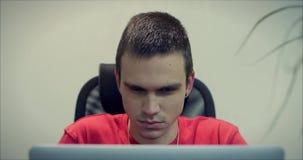Retrato del hombre joven, del programador o del comerciante, sentándose en la oficina con una cara pensativa seria, trabajando en metrajes