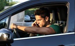 Retrato del hombre joven que conduce con el teléfono móvil Fotografía de archivo