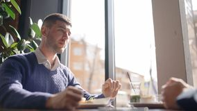 Retrato del hombre joven que escucha su socio mientras que desayunando en café almacen de metraje de vídeo