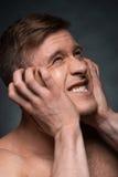Retrato del hombre joven que expresa emociones negativas. imagen de archivo