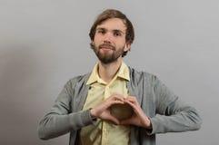 Retrato del hombre joven que hace gesto del corazón Imágenes de archivo libres de regalías