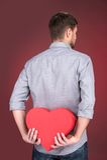 Retrato del hombre joven que lleva a cabo forma del corazón sobre fondo rojo Fotografía de archivo